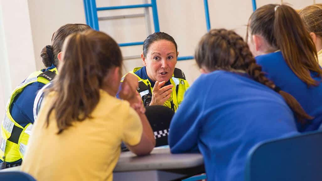 Photo of a female police officer inspiring children