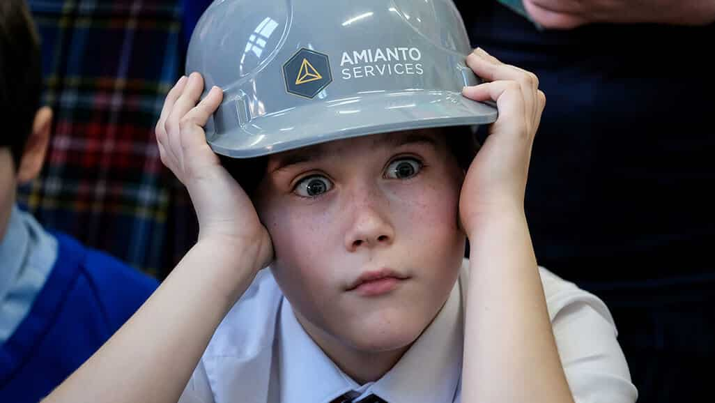 Photo of a boy looking shocked wearing a hardhat from career carousel in the raising aspiration programme