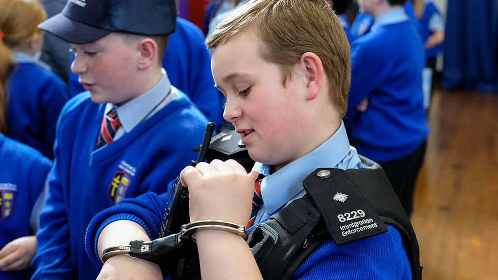 Photo of a boy trying on immigration enforcement uniform from career carousel in the raising aspiration programme