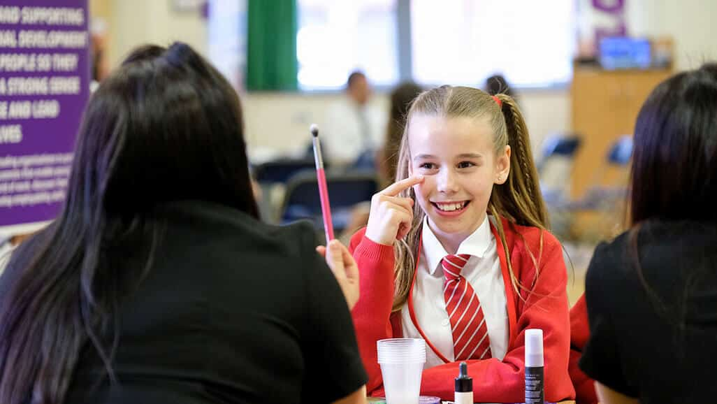 Photo of a girl answering a question from a makeup artist from career carousel in the raising aspiration programme