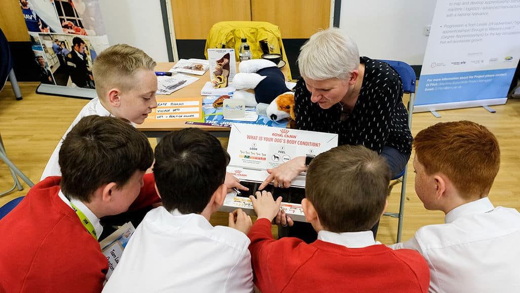 Photo of a vet showing children how they sport a dog body condition from career carousel in the raising aspiration programme