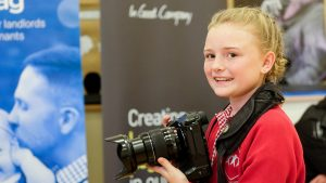 photo of a children from the Raising Aspirations programme taking photos of the Career Carousel event