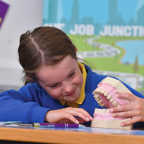 photo of a girl playing with some false teeth from our career carousel event from our raising aspirations programme
