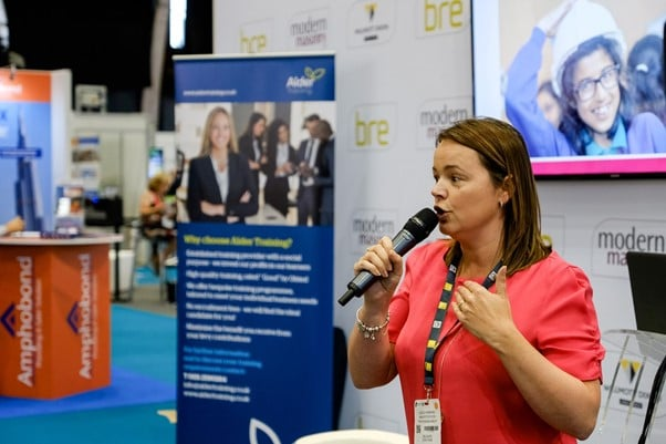 Lesley Burrows speaking at a Positive Footprints event holding a microphone
